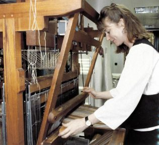 Miss Jill Evason Browning, Senior Design Weave, operating a loom at the studio, 1992