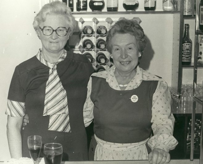 Connie Beak (S.M.) with May Gray (waitress) Serving behind the bar at a retirement party. | JLP Archive Collection