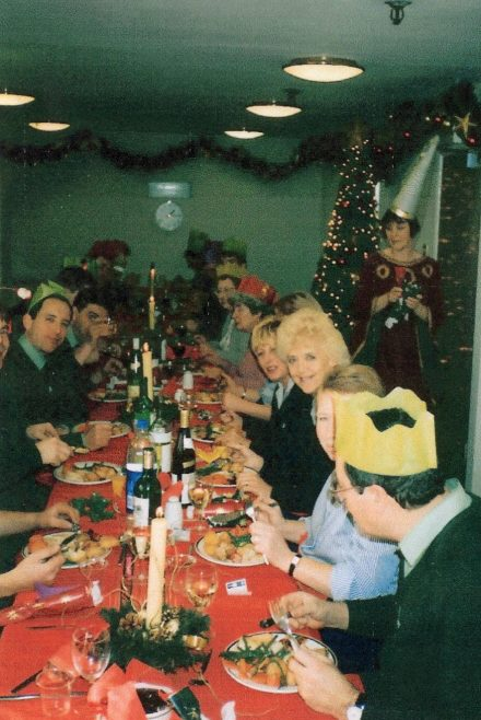 Partners Dave Gardner, Anne Woolcott, Ann Brookes, Anne Stevens, Joe Handman, Josie Pennell and Pam Krisson  tuck in to lunch with Greta Dignan, then Registrar, making sure everyone is served. | From a private collection