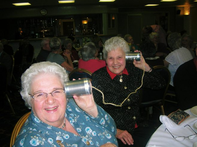 Sally Veysey and Gladys Wingfield with Mobile Phone (tins and string) | JLP Archive Collection