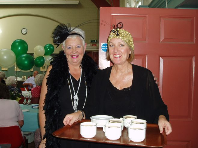 Gloria McLeod and Janet Gardner serve teas to Retired partners at the 75th Anniversary celebration.