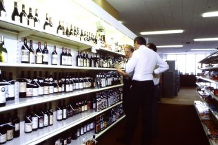 This is a Self Service Wines Layout Review discussion which would have also included wooden shelving behind Wines Counters in some older branches. The top shelf was at an almost unreachable height and required questionable access when moving bottles around during the review process by today's Health & Safety standards. | Merchandising Photo Library